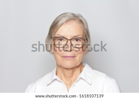 Portrait picture of a senior woman wearing glasses on neutral gray background. Royalty-Free Stock Photo #1618107139