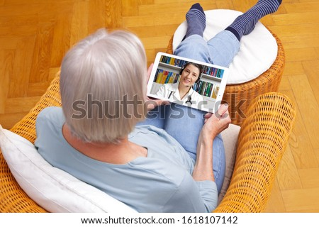 telemedicine concept, old woman with tablet pc during an online consultation with her doctor in her living room. #1618107142