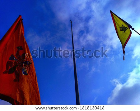 One flagpole with no flag, and two flags of orange and yellow color with the picture of goddess Hanuman, for the celebration of ram navami festival, isolated on cloudy blue sky. #1618130416