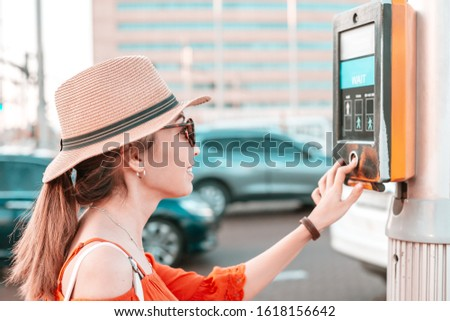 A girl presses a button to cross an adjustable pedestrian crossing on a busy street. Urban development concept #1618156642