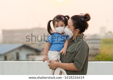 Asian mother and little young daughter wearing mask for prevent dusk pm 2.5 bad air pollution on deck in Bangkok city Thailand 2020.  #1618226614