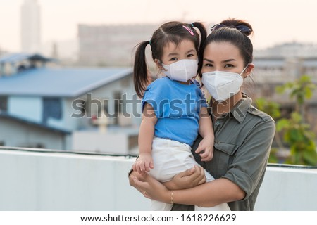 Asian mother and little young daughter wearing mask for prevent dusk pm 2.5 bad air pollution on deck in Bangkok city Thailand 2020.  #1618226629