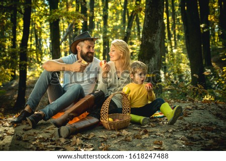 Cheerful family sitting on the grass during a picnic in a park. Young smiling family doing a picnic on an autumns day. Happy family in the park evening light. Autumn family picnic concept