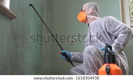 Cleaning and Disinfection at town complex amid the coronavirus epidemic. Professional teams for disinfection efforts. Infection prevention and control of epidemic. Protective suit and mask #1618304938