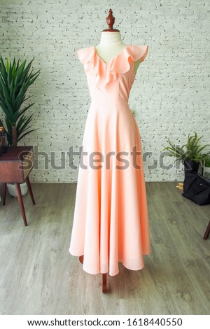 Peach vintage fashion long maxi dress chiffon ruffle neck bridesmaid wedding luxury dress tailor made by a dressmaker, a dress on mannequin sewing dress form in the plain room Royalty-Free Stock Photo #1618440550