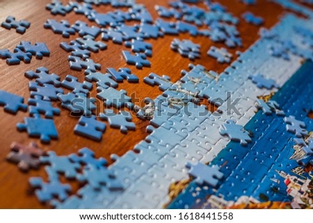 Partially solved jigsaw puzzle with scattered puzzle pieces on the table #1618441558