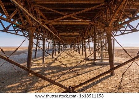 Standing under the rusty iron construction on the downside of a pier #1618511158