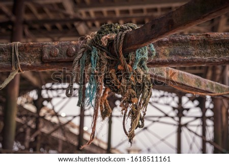 Mooring rope on the rusty iron construction of a pier #1618511161
