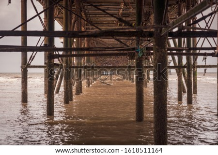 The rusty iron construction on the downside of a pier #1618511164