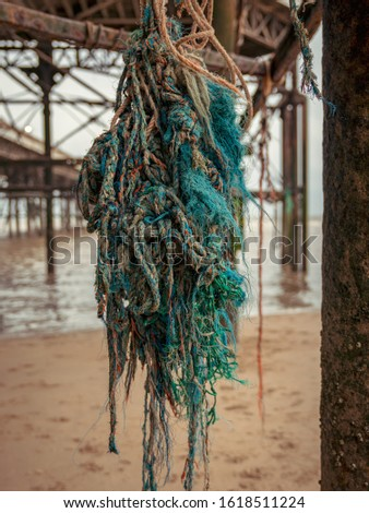 Mooring rope on the rusty iron construction of a pier #1618511224