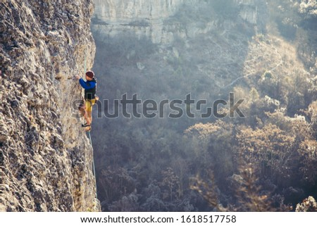 Athletic man climbs very high limestone rock with rope, lead climbing.. Sport climbing outdoor. #1618517758