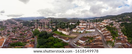 Wide 180 degrees aerial panorama of historical colonial mining city of Ouro Preto in the state of Minas Gerais, Brazil with the São Francisco de Assis church in the middle against an overcast sky #1618549978