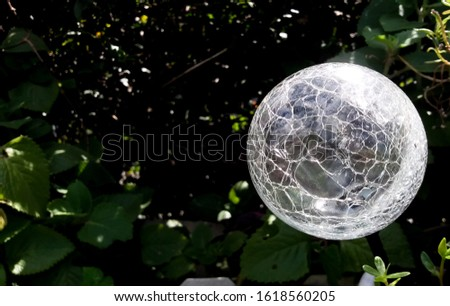 Solar garden light with sphere shape and an abstract pattern design reflecting the sun during the day as it powers with dark blurred foliage in the background #1618560205