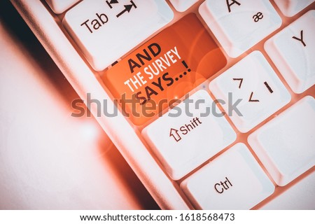 Text sign showing And The Survey Says. Conceptual photo written spoken results of short quiz or exam on internet White pc keyboard with empty note paper above white background key copy space. #1618568473