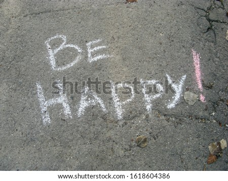 Inscription on the asphalt be happy, chalk written. Wish to be happy, chalk drawing on surface of road. Desire words underfoot. Motivation text outdoors. Lower your head and read important message #1618604386