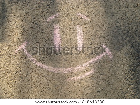 Picture of happy face on asphalt, chalk written. Wish to be happy, chalk drawing on surface of road. Desire words underfoot. Positive image outdoors. Lower your head and read important message #1618613380