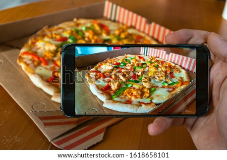 Photo of a chicken and peppers pizza taken with a mobile phone held in a hand. Noisy on purpose shot #1618658101