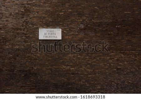 "Deep brown wall with street sign saying ""avenue gate Tiburtina"" #1618693318"