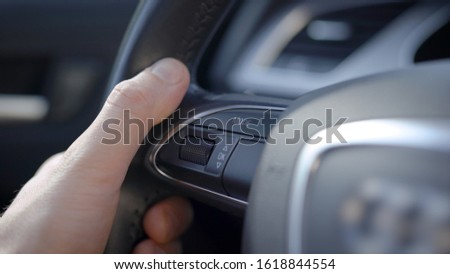 A man drives a car. In the frame there is a multi steering wheel, you can control the vehicle parameters using the buttons and the joystick, right while driving. Leather steering wheel #1618844554