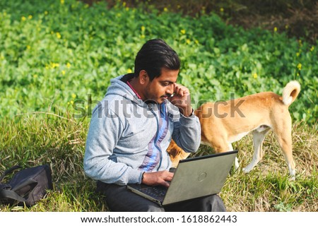 Happy asian successful businessman working on a park and talking on a phone and using a laptop. Man and dog spending time on a sunny day of winter. #1618862443