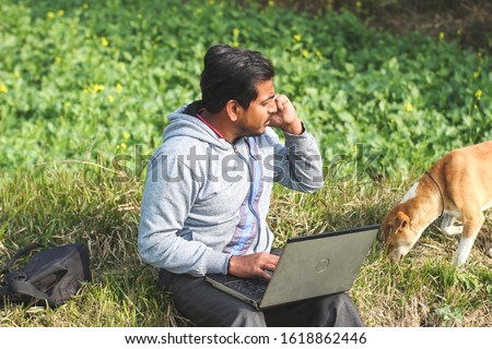 Happy asian successful businessman working on a park and talking on a phone and using a laptop. Man and dog spending time on a sunny day of winter. #1618862446