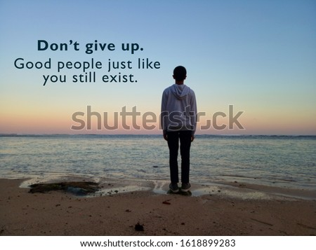 Inspirational motivational quote - Do not give up. Good people just like you still exist. With blurry image of young man standing alone on sand looking at the sunset sunrise color over the sea.