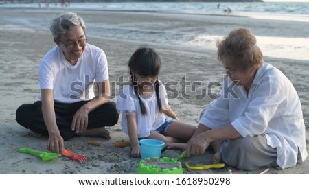 Grandfather and grandmother and niece playing sand on the beach. #1618950298