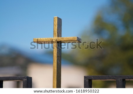 Close up of a small golden religious cross against the blue sky and located on a cemetery in Switzerland. This is a symbol of This is a symbol of hope and salvation #1618950322