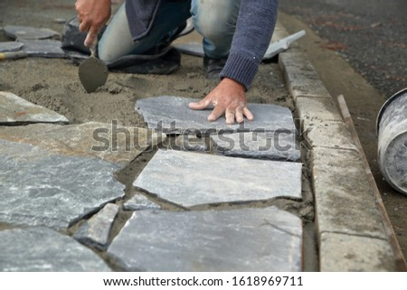Builder  builds / places sidewalk from natural stones #1618969711