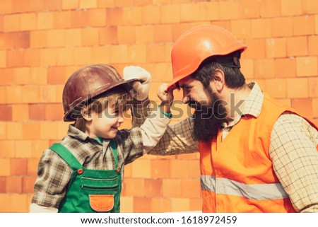 Protective helmets. Construction concept. Brick. Teamwork. Two builders. Child and adult. Professional growth. Career. Carnival professions. A boy and a man at a construction site. #1618972459