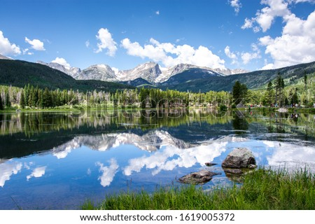 beautiful reflection of the rocky mountains in the sprague lake with green pine forest in the background in summer with blue sky in the rocky mountain national park, colorado, united states of america #1619005372