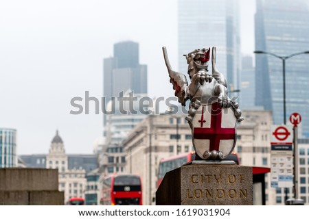 A dragon sculpture with the Coat of Arms of the City of London at the London Bridge. Blurred skyscrapers and red double decker buses in the background - image #1619031904