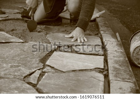 Builder builds sidewalk from natural stones monochrome in sepia color #1619076511
