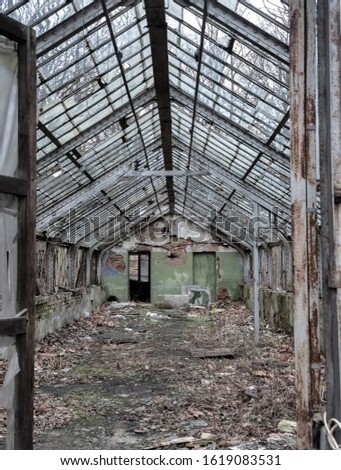 Dilapidated abandoned greenhouse in a city forest park #1619083531