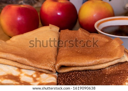 Pancakes. On the table are apples and pancakes folded in a triangle