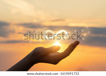 The concept of unlimited Internet. Hand shows the sign of infinity in the sun.