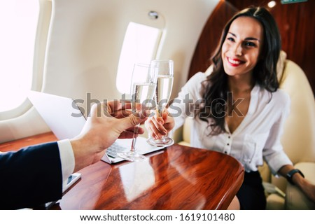 Sparkling champagne. Close-up photo of a cheerful woman, who is clinking with her flute of champagne with her colleague, while celebrating a successful deal during their flight. Royalty-Free Stock Photo #1619101480