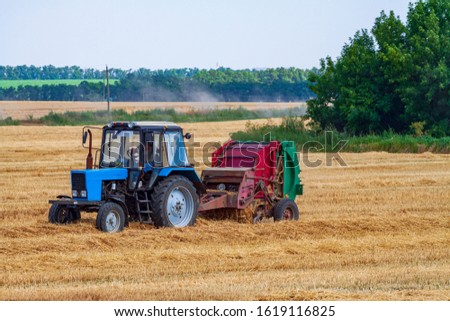 A tractor with a trailed bale making machine collects straw rolls in the field and makes round large bales #1619116825