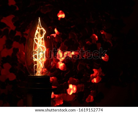 An edison lighbulb glows gently illuminating a red sequin background. Love heart sequins in very soft focus exaggerate the glowing reflection of the bulb. #1619152774