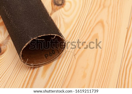 Sandpaper on a wooden background. Stock photo with place for caption.