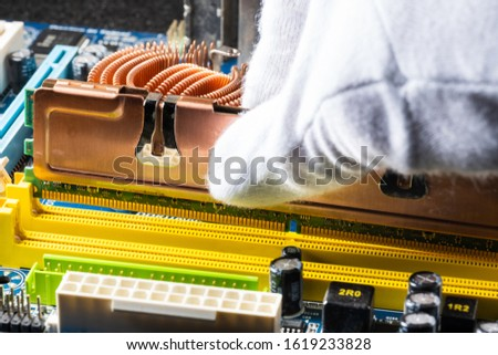 assembling a computer in white gloves, installing RAM with copper plates, macro photo  #1619233828