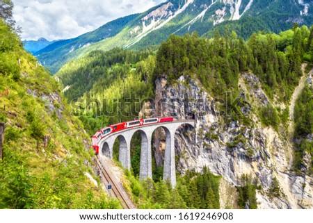 Landwasser Viaduct in summer, Filisur, Switzerland. It is landmark of Swiss Alps. Nice Alpine landscape. Red train of Bernina Express on railroad bridge in mountains. Panoramic view of famous railway. Royalty-Free Stock Photo #1619246908