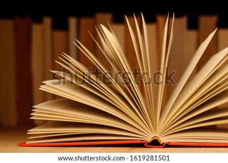 Close up picture of open book on wooden table in front of row of books. Concept of reading books, education, information