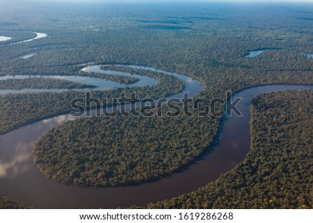 View of the Amazon River from an airplane, dense tropical forest, reflection in the water.