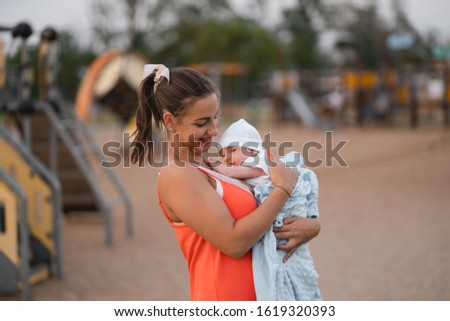 Breast feeding: Young mother breastfeeds her baby boy child in city park standing wearing bright red dress - Son wears white cap - Family values warm color summer scene handheld #1619320393