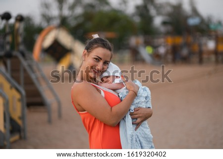 Breast feeding: Young mother breastfeeds her baby boy child in city park standing wearing bright red dress - Son wears white cap - Family values warm color summer scene handheld #1619320402