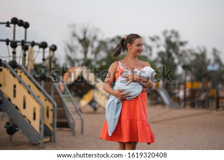 Breast feeding: Young mother breastfeeds her baby boy child in city park standing wearing bright red dress - Son wears white cap - Family values warm color summer scene handheld #1619320408