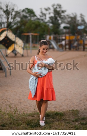 Breast feeding: Young mother breastfeeds her baby boy child in city park standing wearing bright red dress - Son wears white cap - Family values warm color summer scene handheld #1619320411