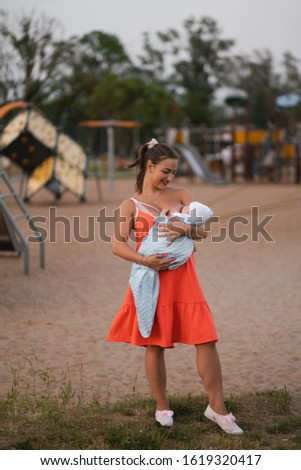 Breast feeding: Young mother breastfeeds her baby boy child in city park standing wearing bright red dress - Son wears white cap - Family values warm color summer scene handheld #1619320417