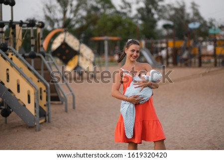 Breast feeding: Young mother breastfeeds her baby boy child in city park standing wearing bright red dress - Son wears white cap - Family values warm color summer scene handheld #1619320420